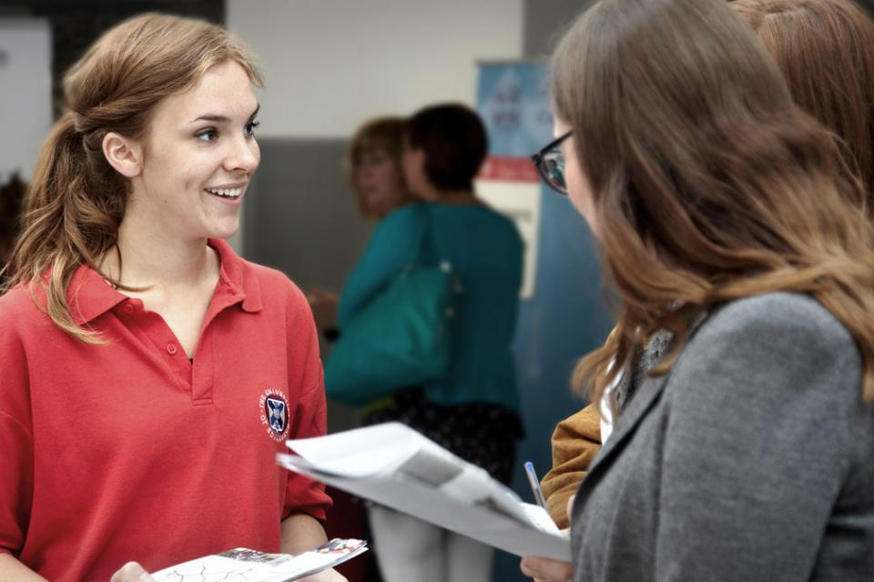 A University of Edinburgh student helper talks to prospective students
